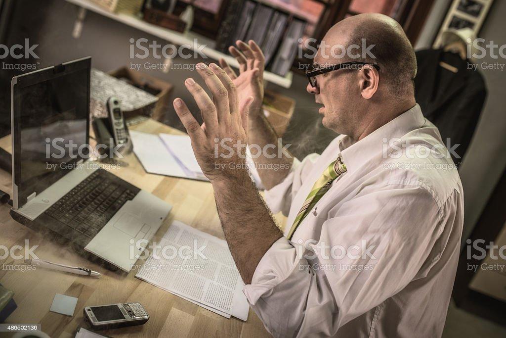 Stressed mature adult businessman using laptop computer stock photo