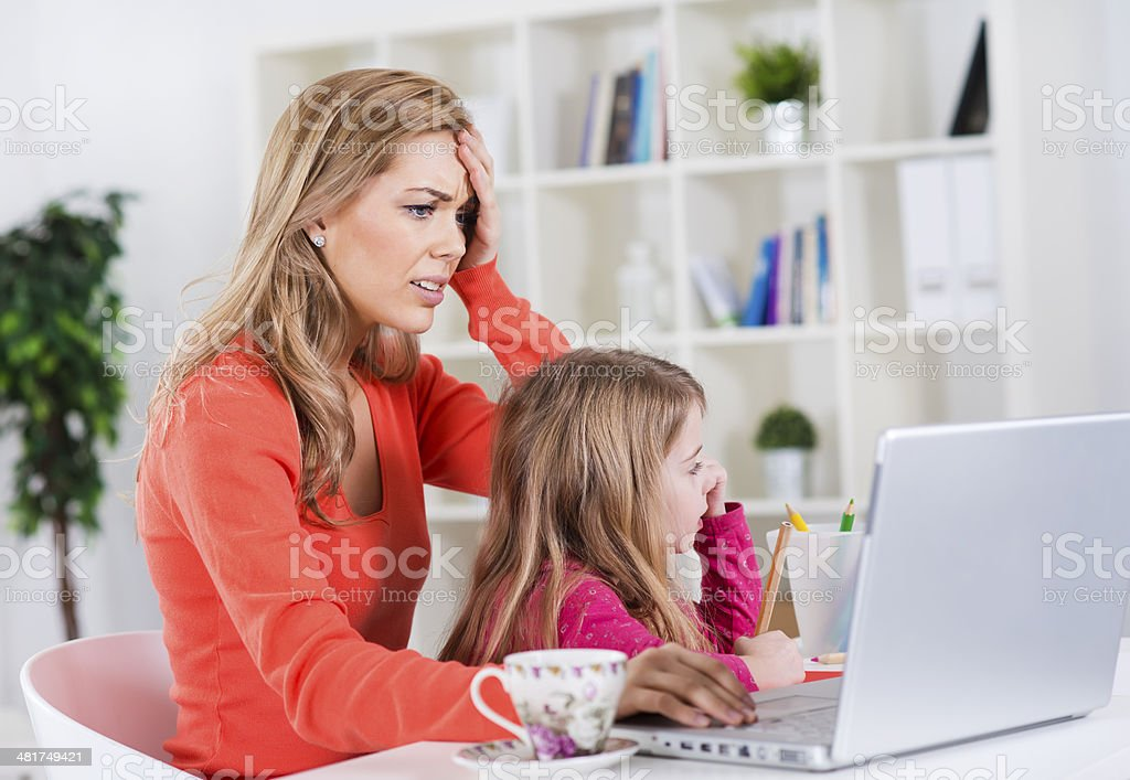 Stressed mother working on computer with child in her lap stock photo