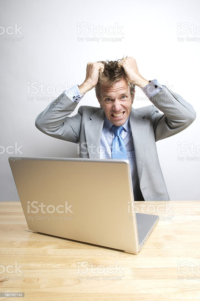 Stressed Office Worker Businessman Tearing His Hair Out at Desk royalty-free stock photo