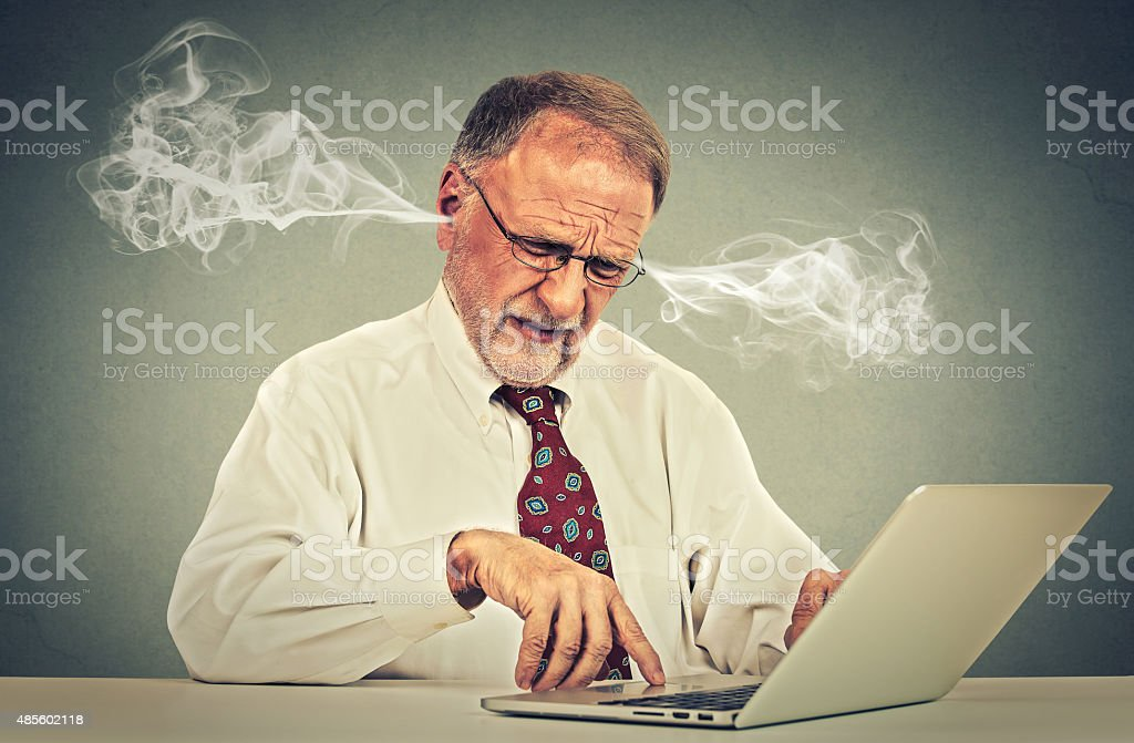Stressed old man using computer blowing steam from ears stock photo