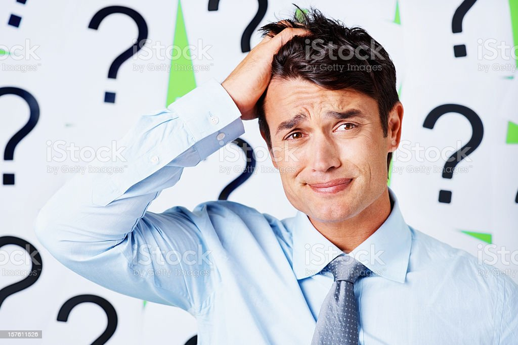 Stressed out business executive against question mark signs royalty-free stock photo