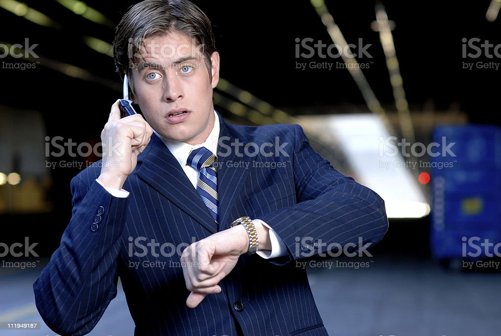 Stressed Out Businessman on Cellphone checks Watch Downtown royalty-free stock photo