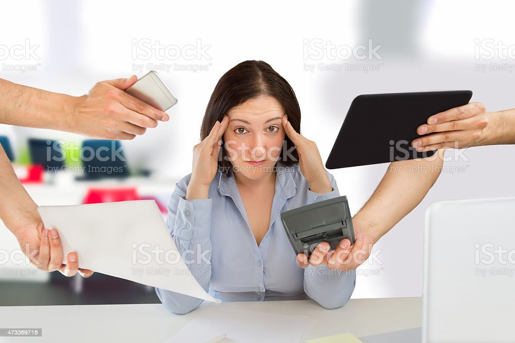 Stressed out woman surrounded by business distractions stock photo