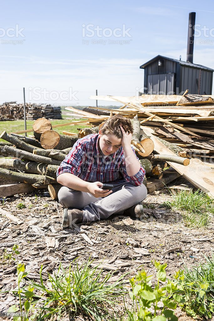 Stressed, sad teenaged boy sitting by a farm woodpile royalty-free stock photo