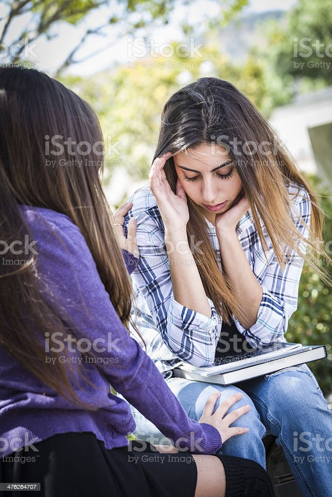 Stressed Sad Young Mixed Race Girl Being Comforted By Friend stock photo