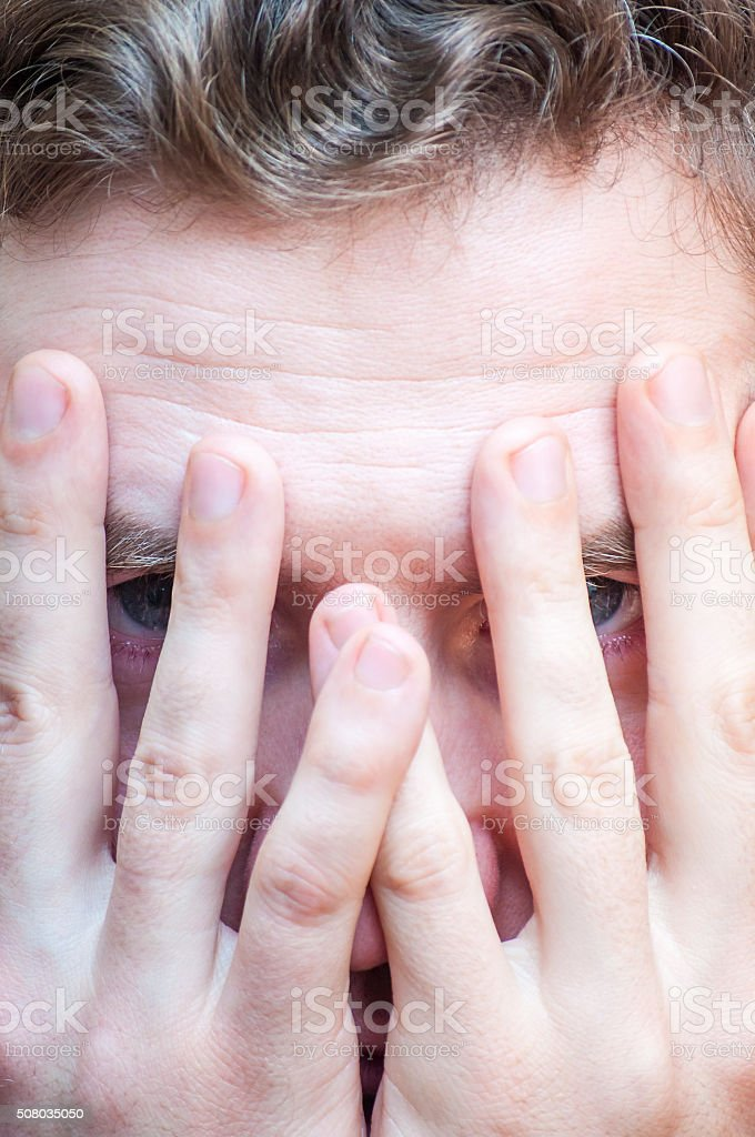 Stressed, scared man hiding by covering his face with palms stock photo