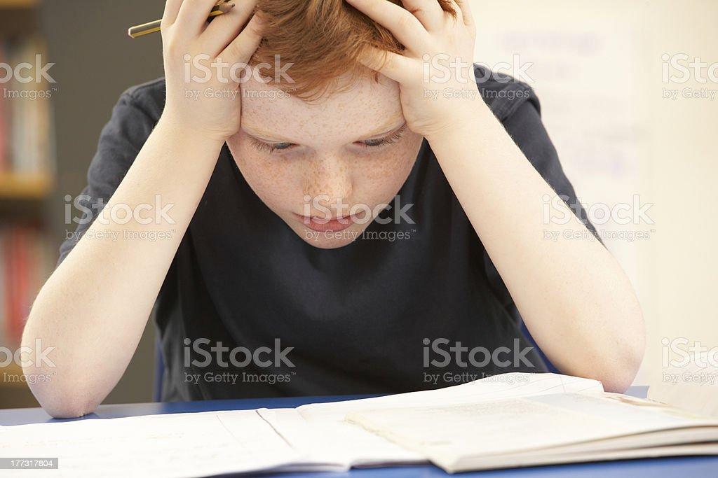 Stressed Schoolboy Studying In Classroom stock photo