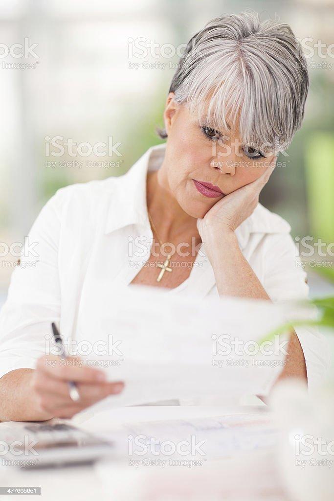 stressed senior woman paying her bills royalty-free stock photo