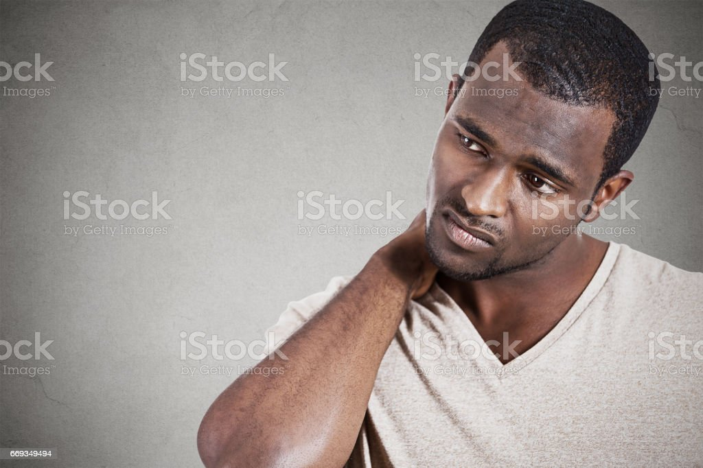stressed, unhappy young handsome man with really bad neck pain stock photo