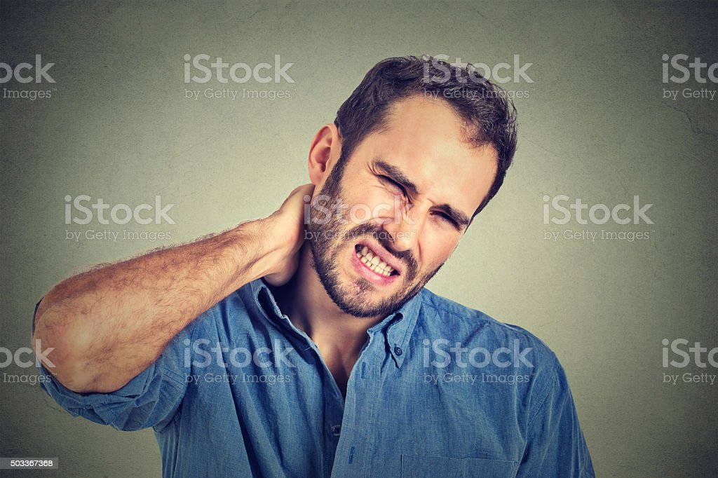 stressed, unhappy young man with bad neck pain stock photo