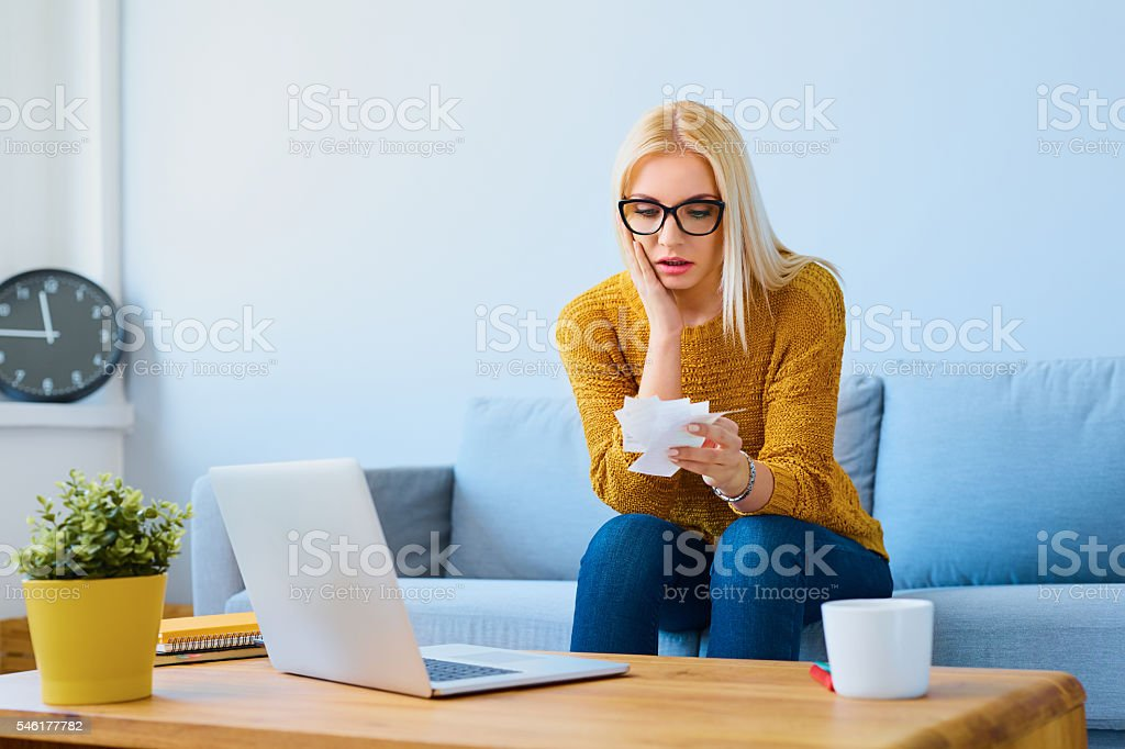 Stressed woman counting home expensses stock photo