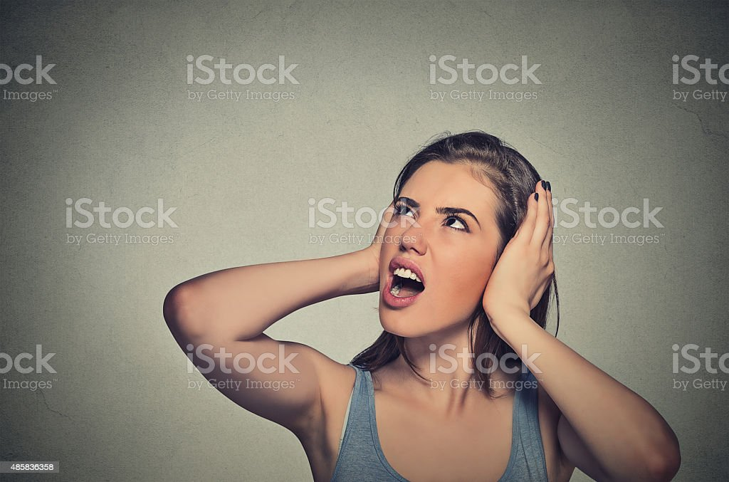 stressed woman covering her ears looking up stock photo