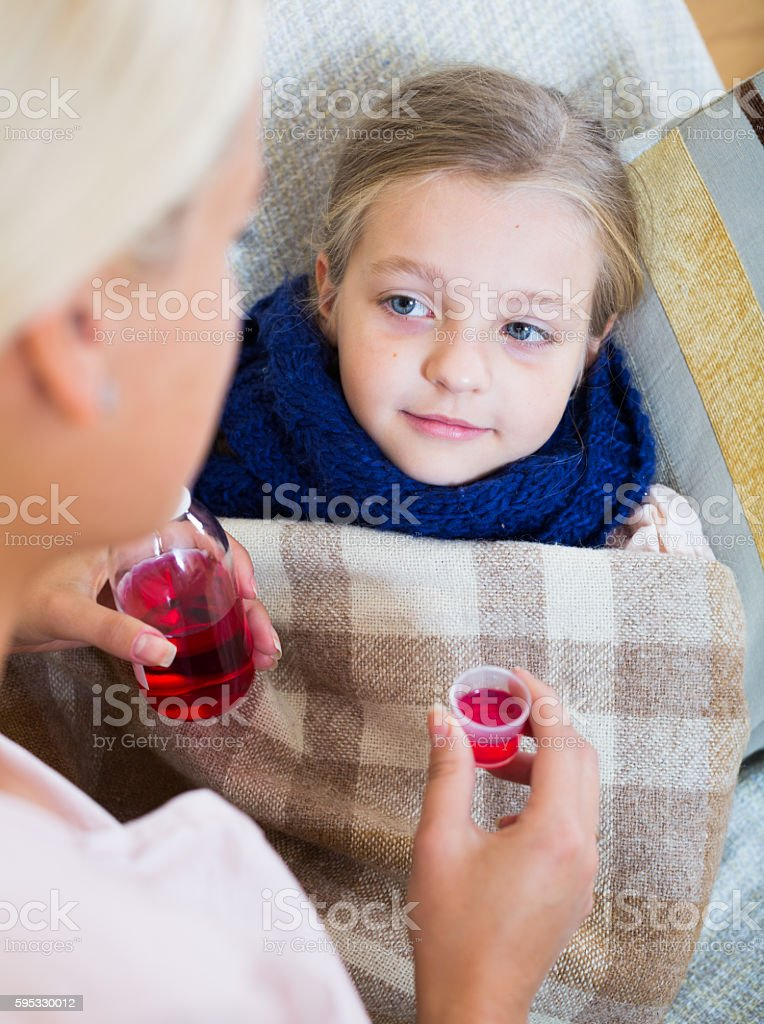 Stressed woman giving liquid medicine to little girl with grippe stock photo