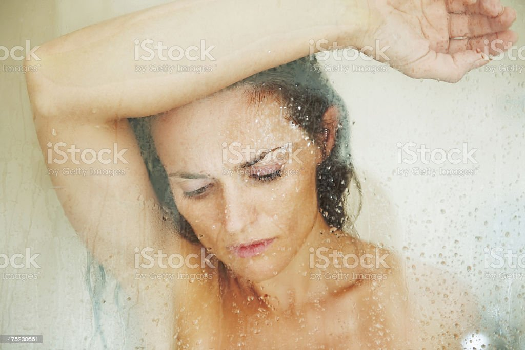 stressed woman leaning on weeping glass shower door royalty-free stock photo