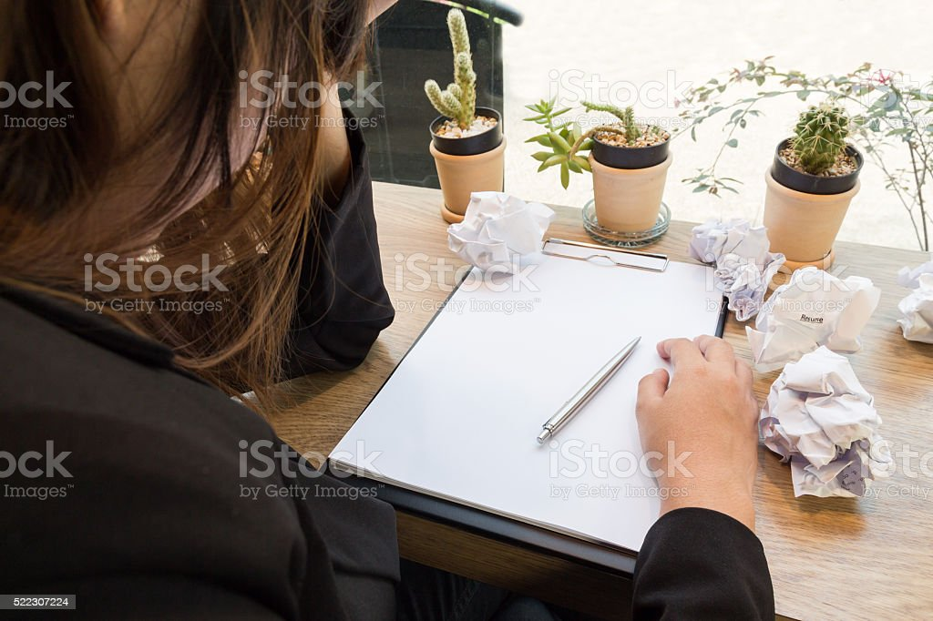 Stressed woman sitting at wooden desk with paper balls stock photo