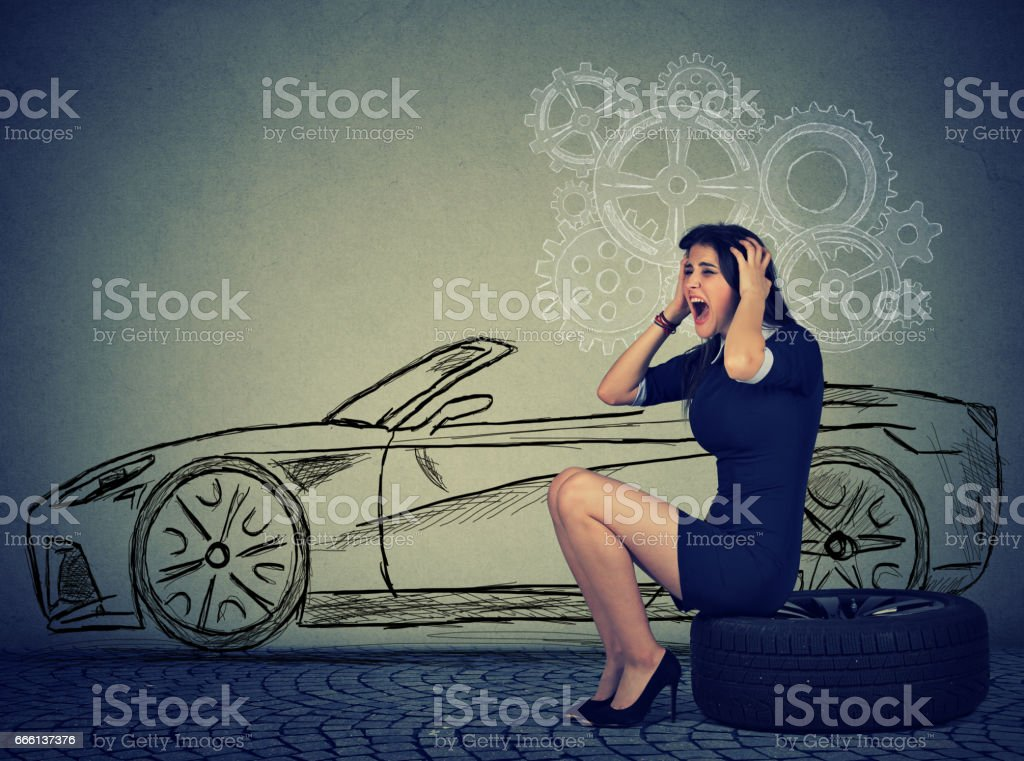 Stressed woman with broken down car flat tire in the middle of the street stock photo
