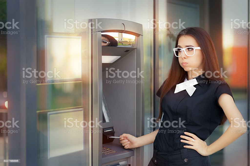 Stressed Woman with credit card at ATM stock photo