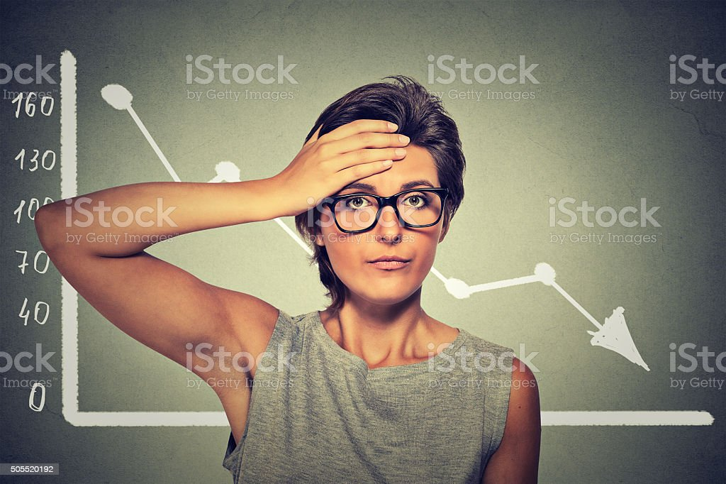 Stressed woman with financial market chart graphic going down stock photo