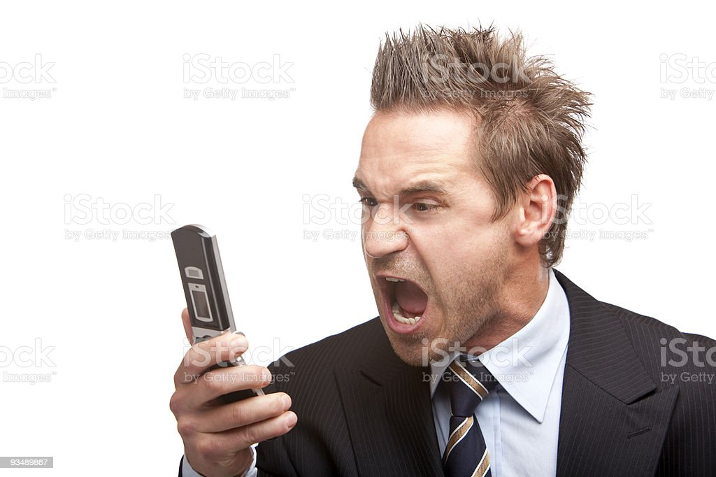 A stressed, young businessman screaming into phone royalty-free stock photo