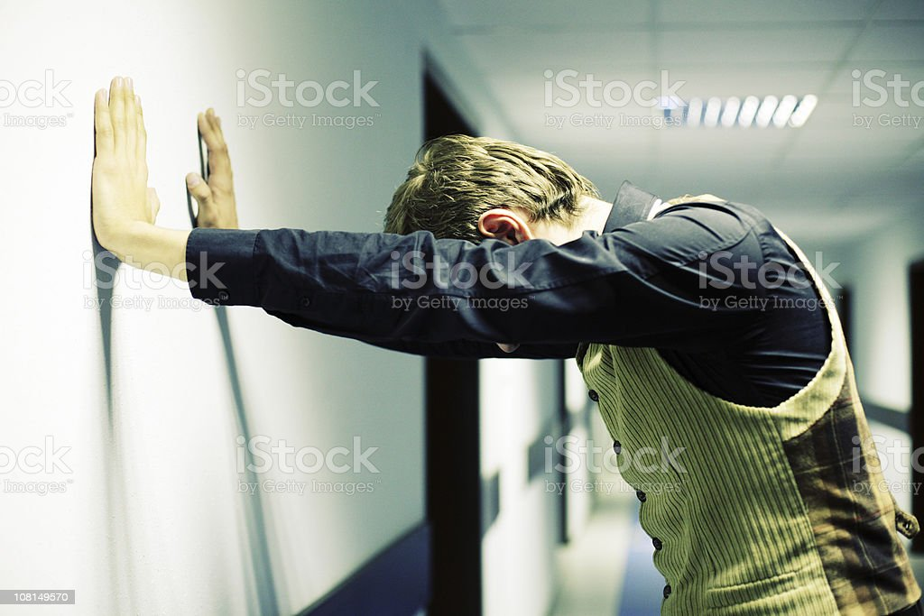 Stressed Young Businessman Standing in Office Hallway royalty-free stock photo