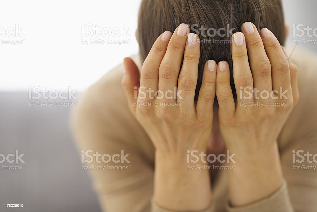 stressed young woman sitting on couch stock photo