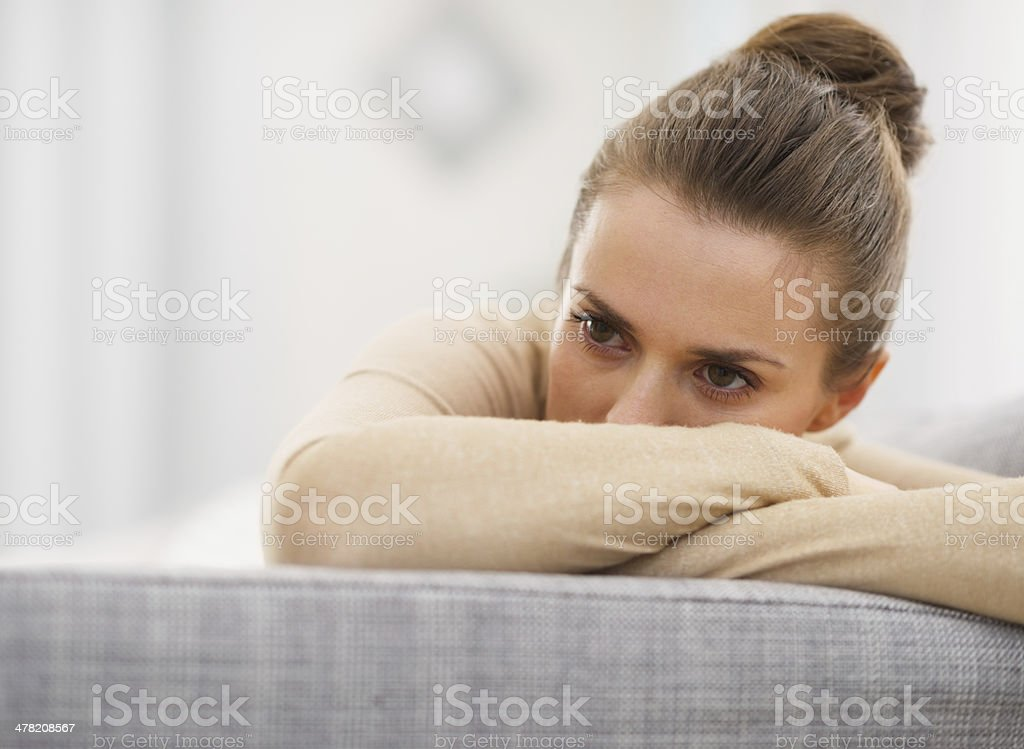 stressed young woman sitting on sofa stock photo