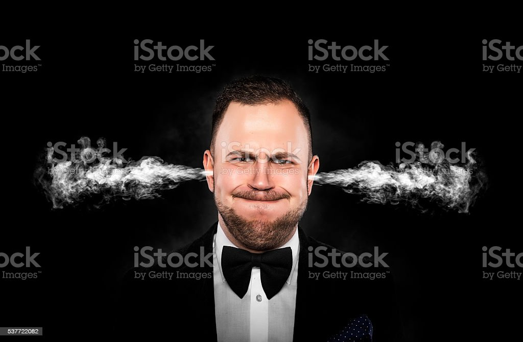 Stressful man with smoke coming out from his ears. stock photo