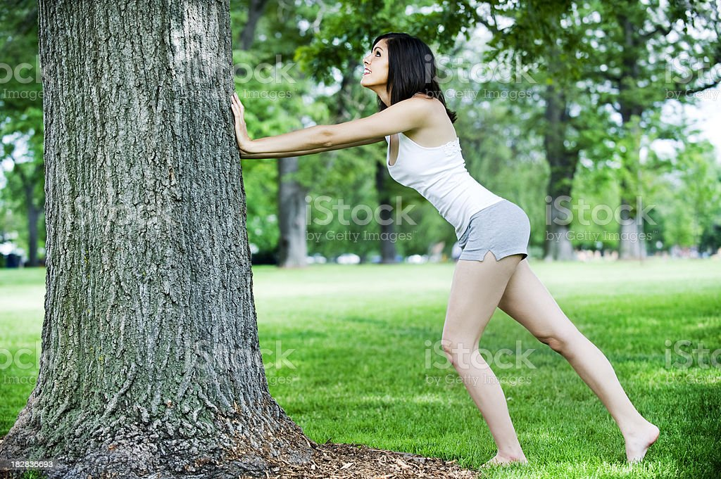 Stretching against a Tree royalty-free stock photo