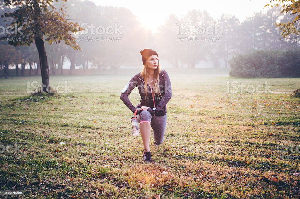Young sporty woman exercising before jogging in park . She is...