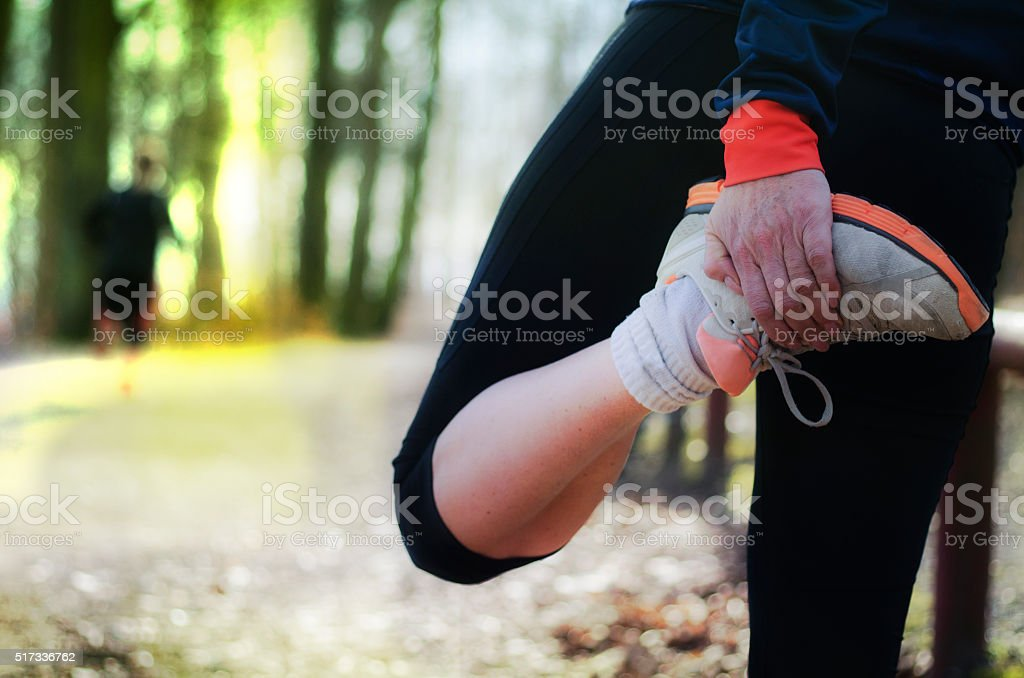 Stretching exercises after running in the forest stock photo