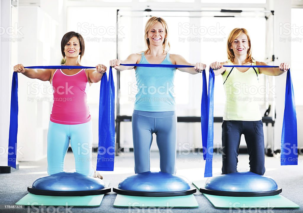 Women doing Pilates exercises with rubber bands.