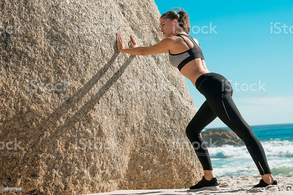 stretching for the workout on the beach stock photo