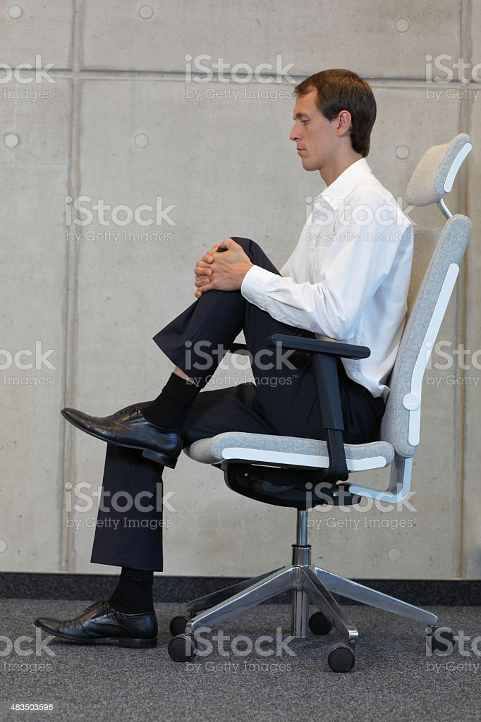 stretching in office on chair stock photo