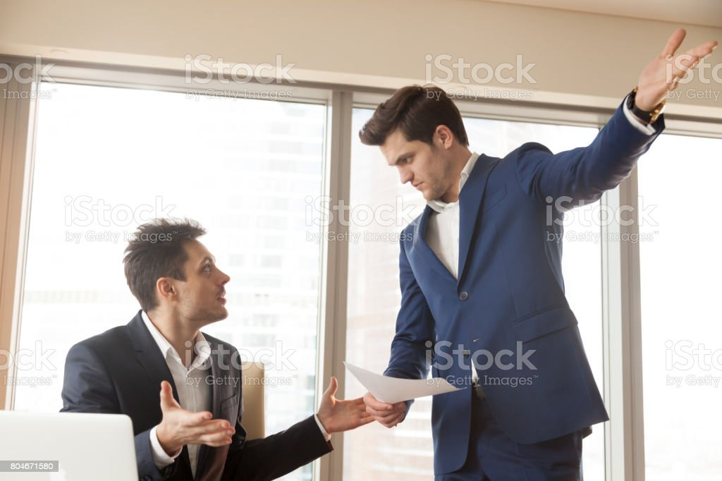 Strict boss firing incompetent employee for bad work at workplace stock photo