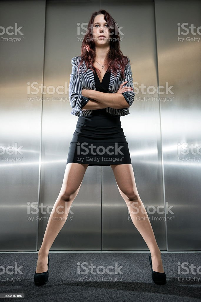 strict businesswoman standing with arms crossed at elevator stock photo