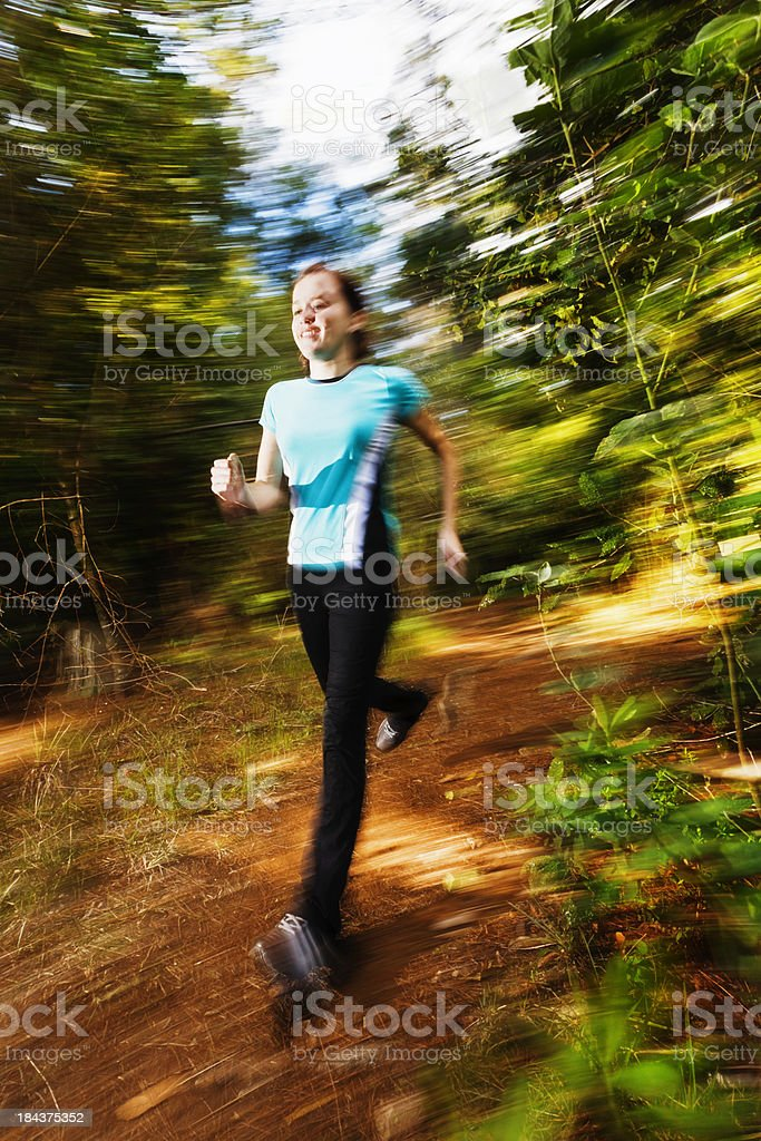 Striding out! Young, motion-blurred, happy female runner in forest royalty-free stock photo