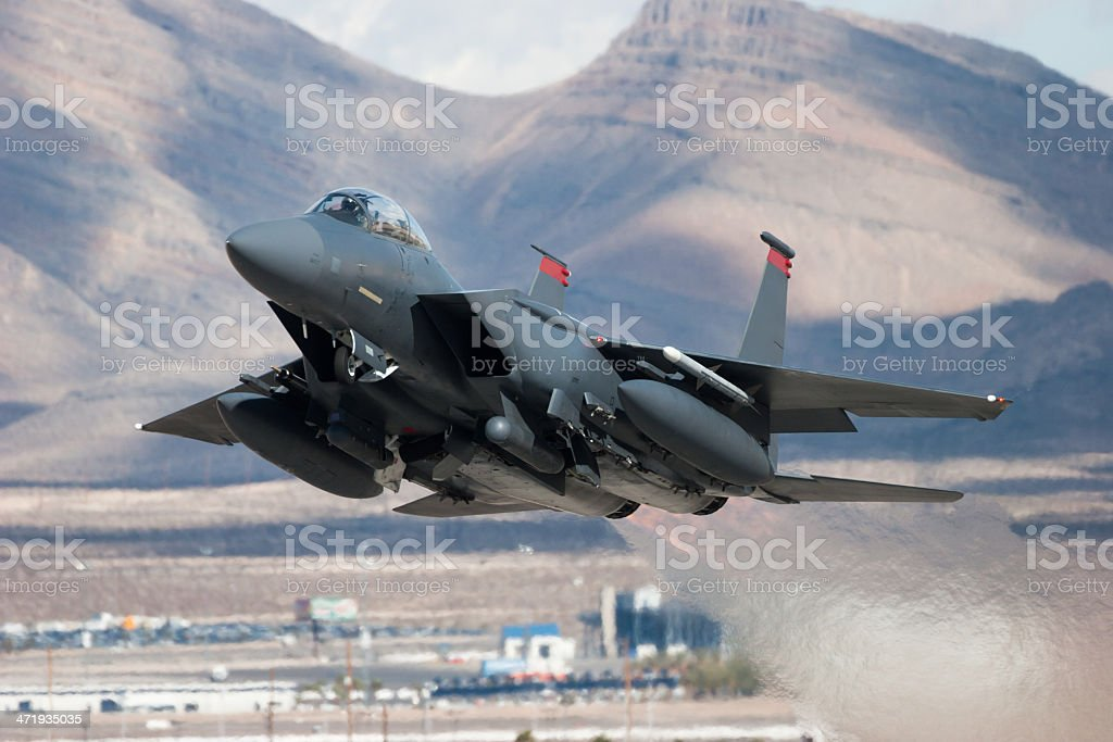 F-15E Strike Eagle flying past mountains stock photo