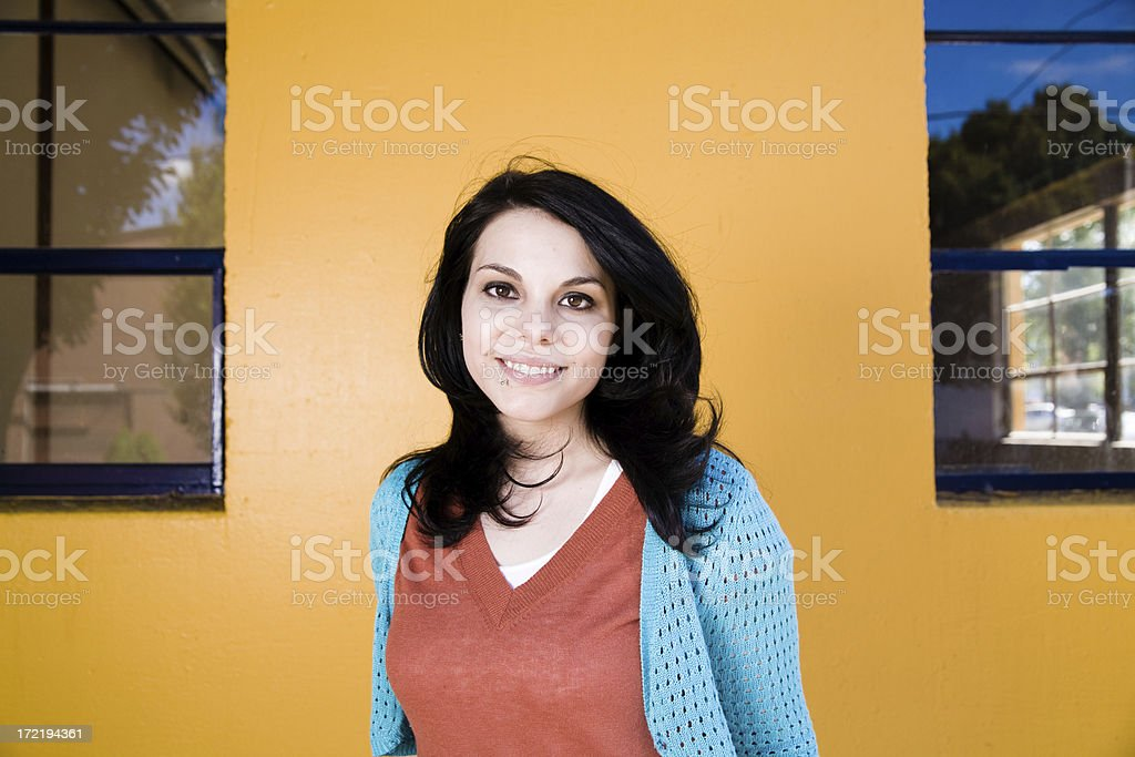 striking young woman infront of yellow wall royalty-free stock photo