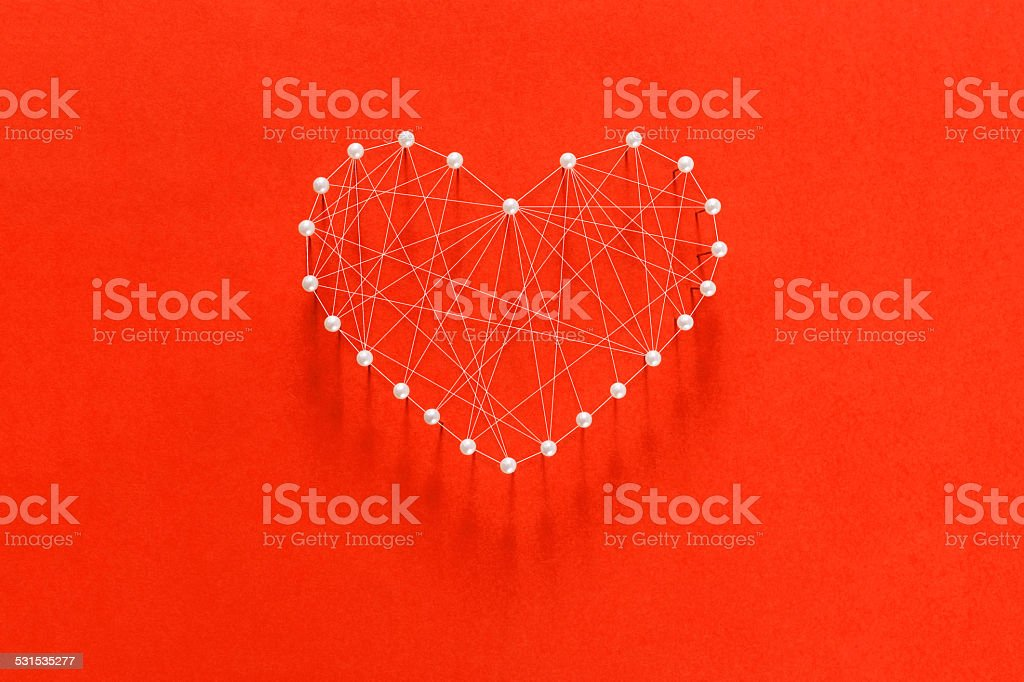 string and white pins shaped heart on red background stock photo