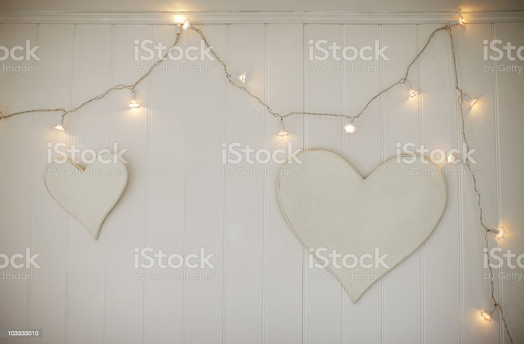String lights and hearts hanging on wall stock photo