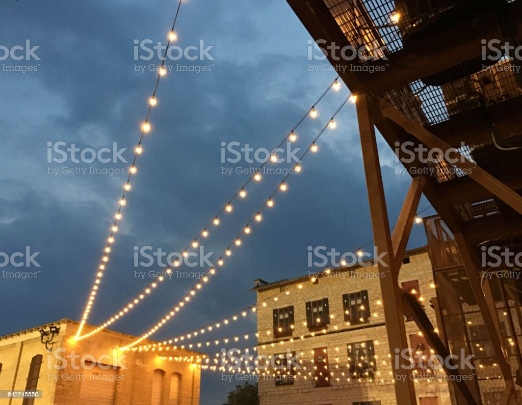 A string of light hang over an outdoor party. stock photo