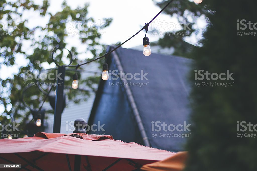 Strings lights on an outdoor restaurant patio stock photo