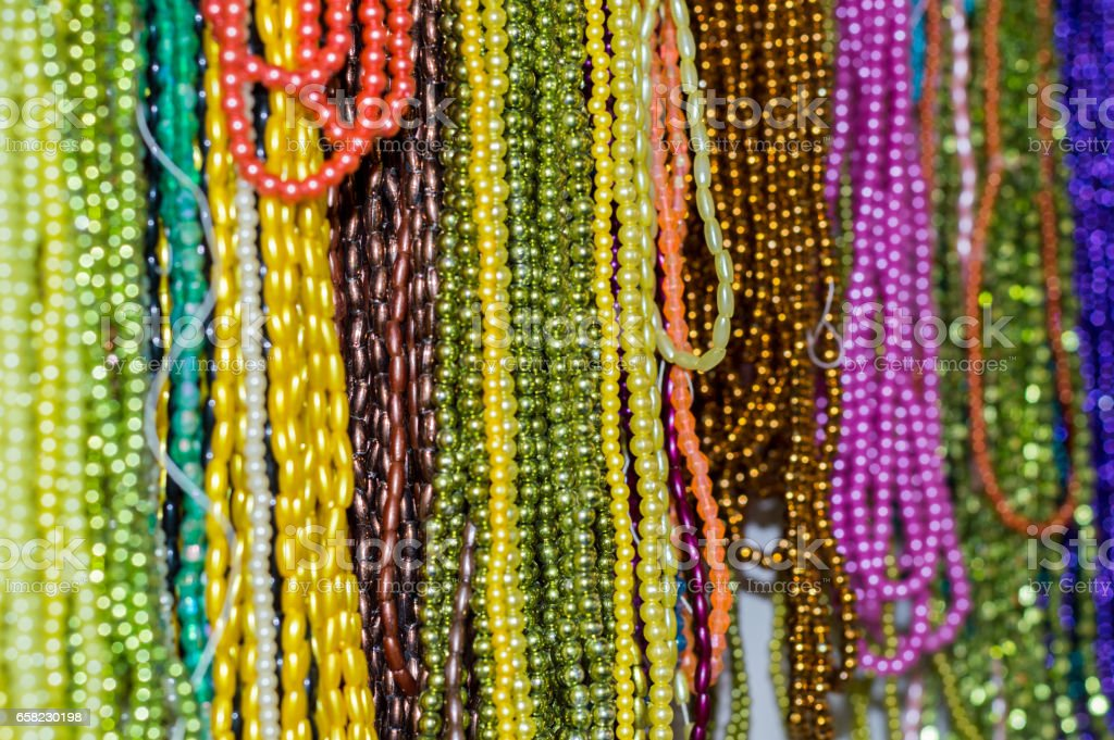 Strings of colorful beads hung at outdoor crafts market stock photo