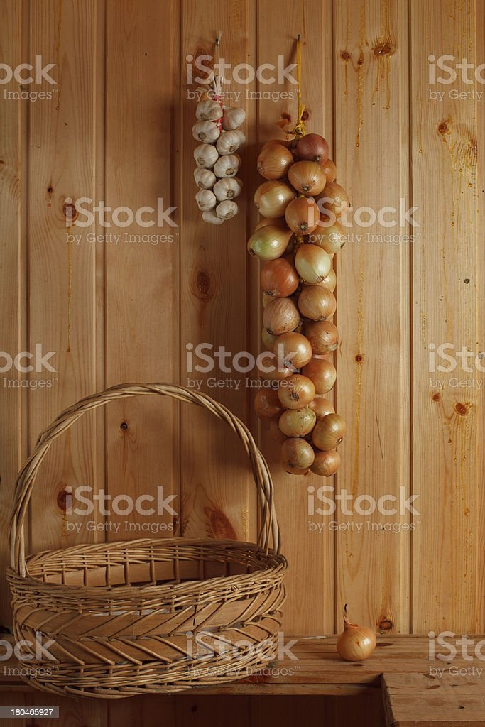strings of white onions and garlic with basket royalty-free stock photo