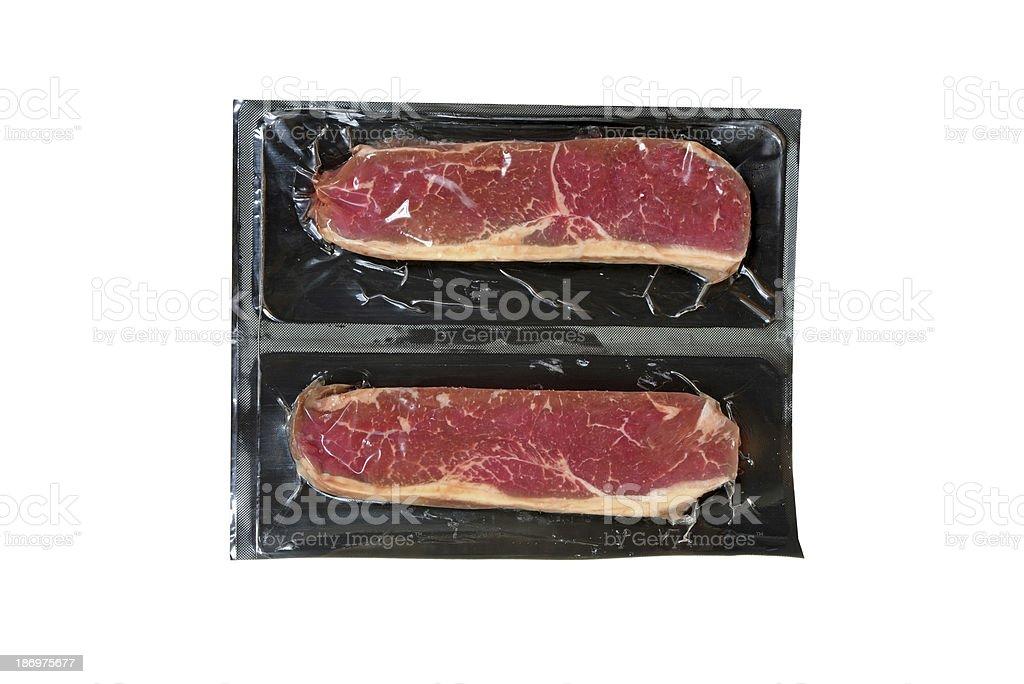 strip loin steak in plastic wrap stock photo