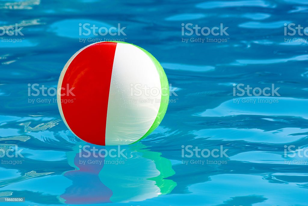 striped ball in the swimming pool sunny day royalty-free stock photo