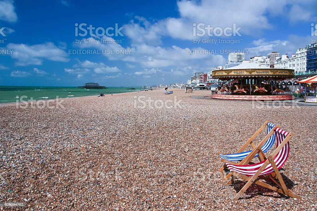 striped deckchairs on brighton beach uk stock photo