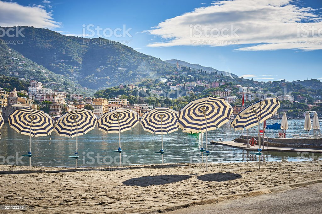 Striped parasols in a line at beach stock photo