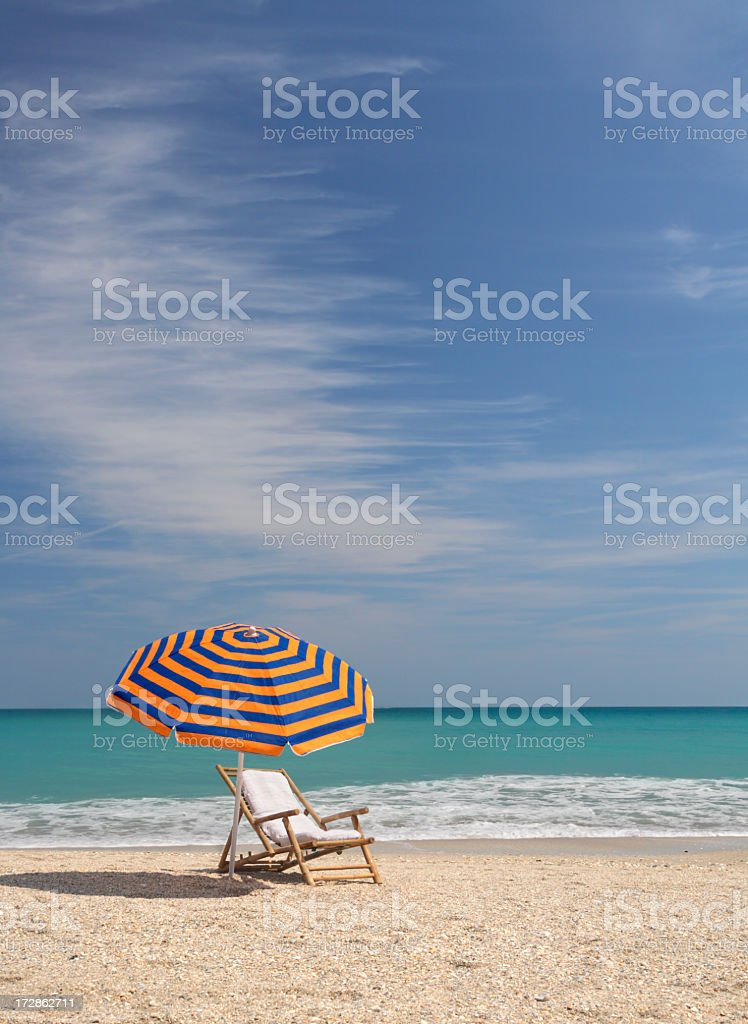 striped umbrella and bamboo chair royalty-free stock photo