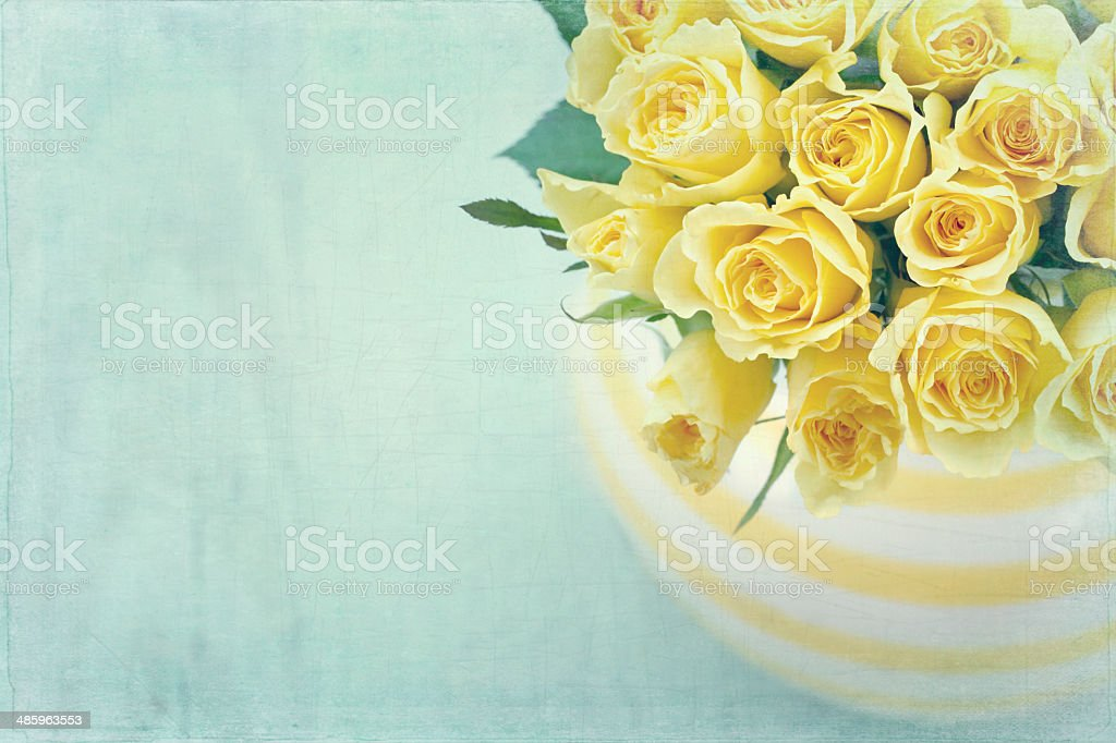 Striped vase with a bouquet of yellow roses stock photo